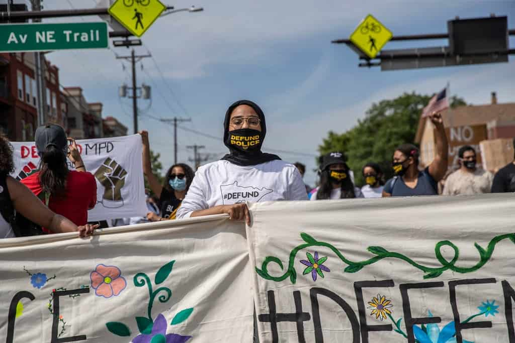 Protesters walk in a Defund the Police march Saturday, in Minneapolis.Credit...Victor J. Blue for The New York Times